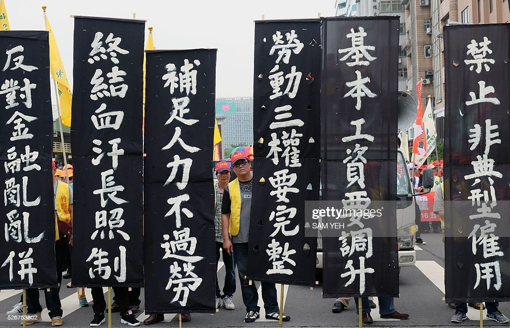 Laborers from different groups display signs that read 'raise the basic labor's salary' during a demonstration to mark the annual Labor's Day in Taipei on May 1, 2016. Thousands local labors and foreign workers march on the streets in Taipei to demand to protect their basic labor's rights. / AFP / SAM YEH