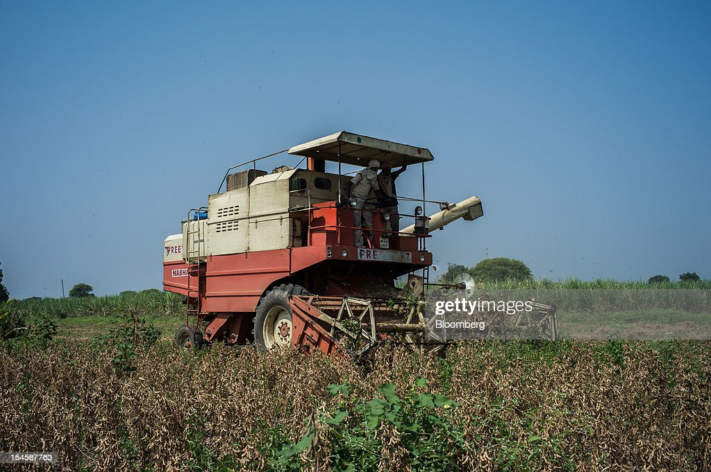 Laborers harvest soybeans with a combine harvester in the district of Burhanpur, Madhya Pradesh, India, on Friday, Oct. 19, 2012. Global soybean consumption will drop about 3 million metric tons in 2012-2013 as record prices curb demand for the oil made from the oilseed for food and biofuel, Thomas Mielke, executive director of Oil World, said. Photographer: Sanjit Das/Bloomberg via Getty Images