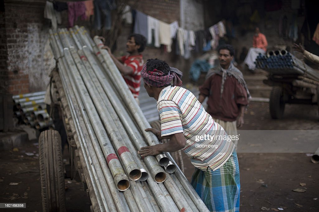 Laborers load a cart with metal pipes in Kolkata, India, on Tuesday, Feb. 19, 2013. India's slowest economic expansion in a decade is limiting profit growth at the biggest companies even as foreigners remain net buyers of the nation's stocks, according to Kotak Institutional Equities. Photographer: Brent Lewin/Bloomberg via Getty Images