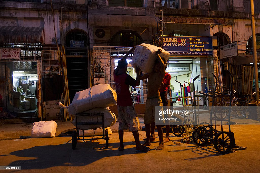 Laborers load bags of clothing at night in Yangon, Myanmar, on Tuesday, Jan. 22, 2013. Myanmar cleared about $1 billion in overdue debt with the Asian Development Bank and World Bank using a bridge loan from Japan, opening the door for increased lending as the country seeks to overhaul its infrastructure. Photographer: Brent Lewin/Bloomberg via Getty Images