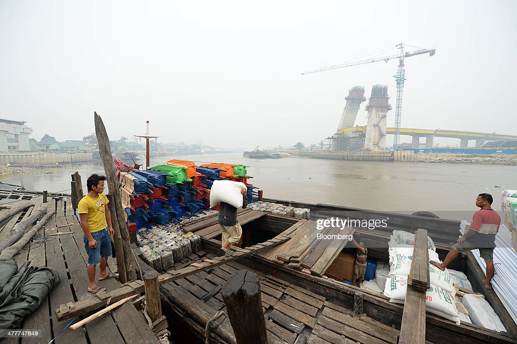 Laborers load goods onto a boat as a new bridge stands under construction across the Siak river in Pekanbaru, Riau Province, Indonesia on Friday, March 7, 2014. Indonesian central bank Governor Agus Martowardojo embarked on the country's most aggressive rate-increase cycle in eight years within a month of taking the helm in May to shore up the rupiah and damp price pressures. Photographer: Dimas Ardian/Bloomberg via Getty Images