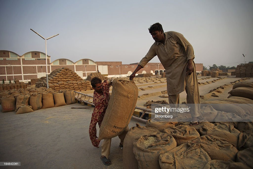 Laborers move bags of rice at a rice-processing factory in the Chiniot district of Punjab province, Pakistan, on Saturday, Oct. 13, 2012. Rice exports from Pakistan, the fourth-largest shipper, are set to rebound from November with the new harvest after a rally in domestic prices and cheaper supplies from India cut shipments, a traders' group said. Photographer: Asad Zaidi/Bloomberg via Getty Images