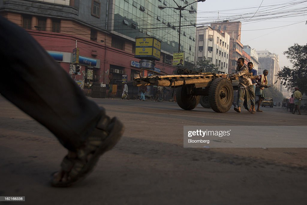 Laborers push a cart on a street in Kolkata, India, on Tuesday, Feb. 19, 2013. India's slowest economic expansion in a decade is limiting profit growth at the biggest companies even as foreigners remain net buyers of the nation's stocks, according to Kotak Institutional Equities. Photographer: Brent Lewin/Bloomberg via Getty Images