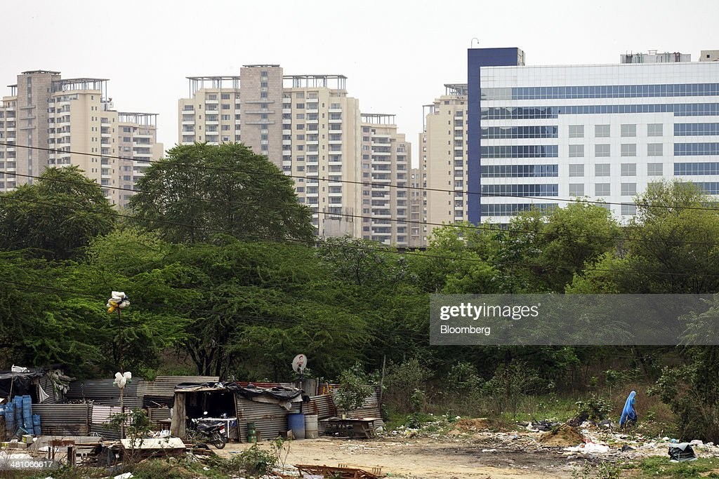 Laborers' shacks stand in front of new commercial and residential buildings in Gurgaon, India, on Wednesday, March 26, 2014. Indian stocks rose, sending the benchmark index to a record, after the rupee rose to an eight-month high and sovereign bonds gained on speculation the worlds largest democracy will elect a government capable of reviving economic growth. Photographer: Kuni Takahashi/Bloomberg via Getty Images