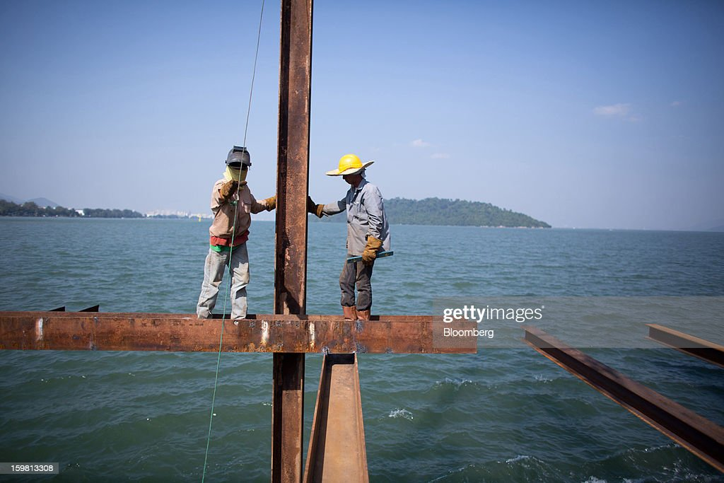 Laborers stand on a beam as they work during construction of the Penang Second Bridge in the town of Batu Maung on Penang Island, Malaysia, on Thursday, Jan. 17, 2013. Penang, a base for the spread of British influence in the 18th century, was the center of a manufacturing push in Malaysia's shift from rubber and tin production in the 1970s, attracting companies including Intel Corp. and Robert Bosch GmbH to assemble chips and build car radios. Photographer: Lam Yik Fei/Bloomberg via Getty Images