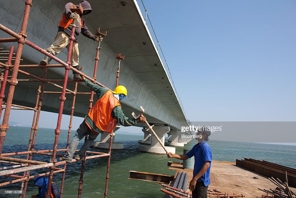 Laborers stand on scaffolding as they work during construction of the Penang Second Bridge in the town of Batu Maung on Penang Island, Malaysia, on Thursday, Jan. 17, 2013. Penang, a base for the spread of British influence in the 18th century, was the center of a manufacturing push in Malaysia's shift from rubber and tin production in the 1970s, attracting companies including Intel Corp. and Robert Bosch GmbH to assemble chips and build car radios. Photographer: Lam Yik Fei/Bloomberg via Getty Images