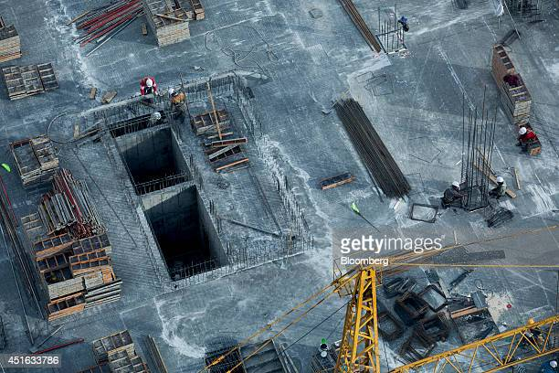 Laborers stand on the roof of a building under construction in Ulaanbaatar Mongolia on Friday June 20 2014 Mongolia growth has been held up...