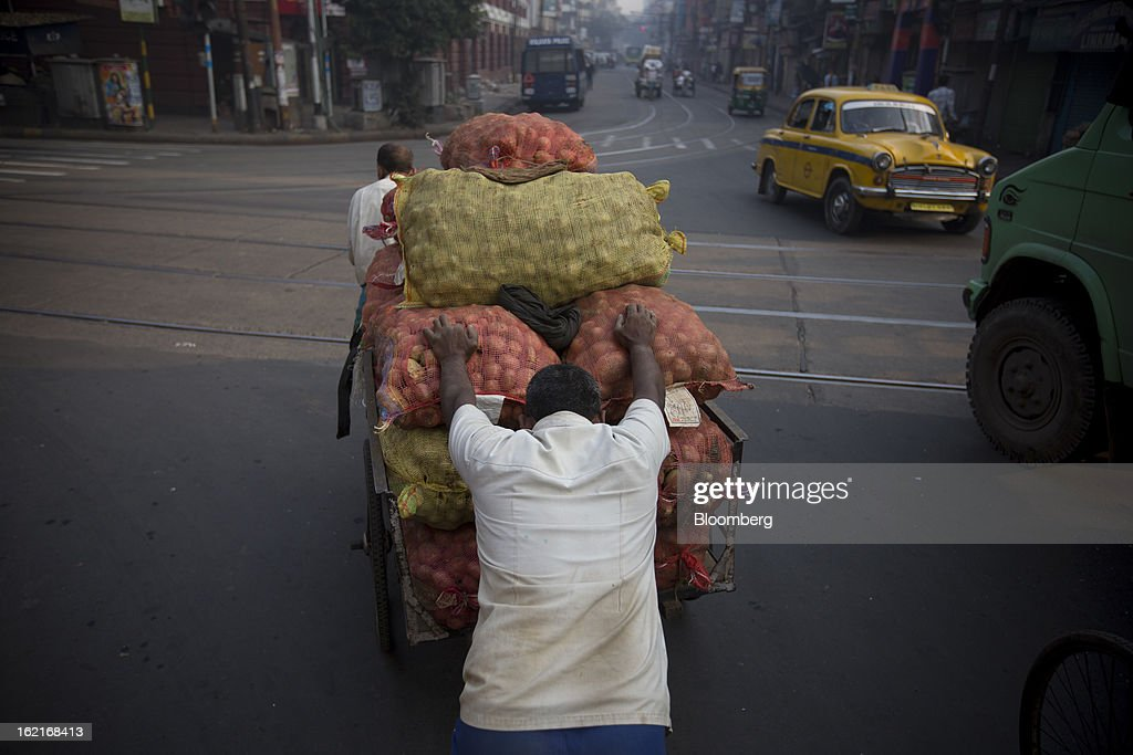 Laborers transport potatoes on a cart across as street in Kolkata, India, on Tuesday, Feb. 19, 2013. India's slowest economic expansion in a decade is limiting profit growth at the biggest companies even as foreigners remain net buyers of the nation's stocks, according to Kotak Institutional Equities. Photographer: Brent Lewin/Bloomberg via Getty Images