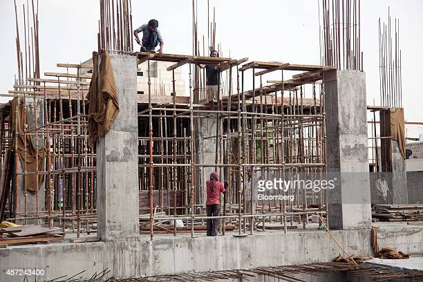 Laborers work at a construction site in Jaipur Rajasthan India on Monday Oct 13 2014 Indias retail inflation slowed more than economists had...