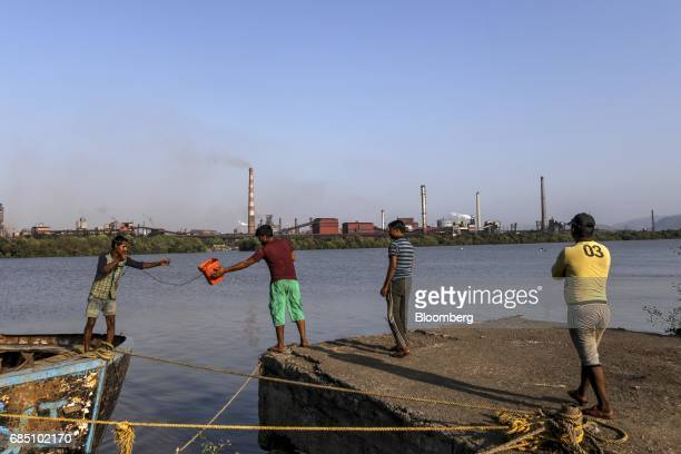 Laborers work at a pier near the JSW Steel Ltd manufacturing facility in Dolvi Maharashtra India on Thursday May 18 2017 JSW India's biggest producer...