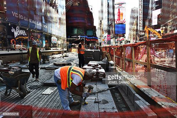 Laborers work on a footpath and road way construction site in Times Square on October 8 2014 in New York The September US employment report showed a...