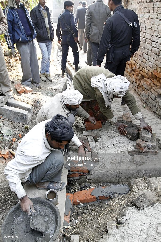 Laborers working on village street ahead of Chief Minister Akhilesh Yadav's visit to native village of Delhi Gang Rape victim on January 10, 2013 in Ballia, India. Uttar Pradesh administration is working overtime to prepare for Chief Minister Akhilesh Yadav's expected visit on January 12 to give a cheque to the father of the gangrape victim who died in Singapore after being brutally raped and tortured on a bus.