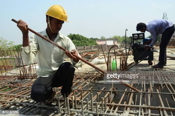 A labour is working during Flyover construction at Shahmatganj in day before International Labour Day on April 30 2017 in Bareilly India