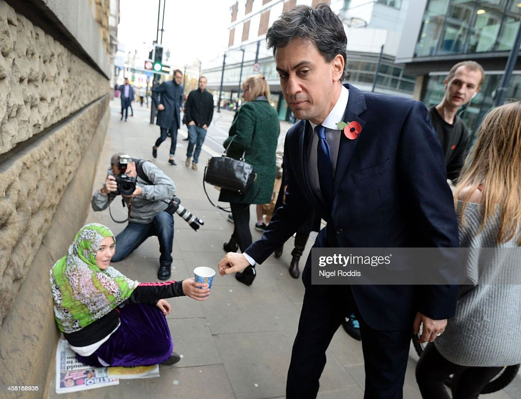 Labour leader Ed Miliband donates money to a woman as he walks to a meeting with UK council leaders at the Town Hall on October 31, 2014 in Manchester, England. A recent poll has predicted that Labour could lose it's Scottish seats to the Scottish National party next year.