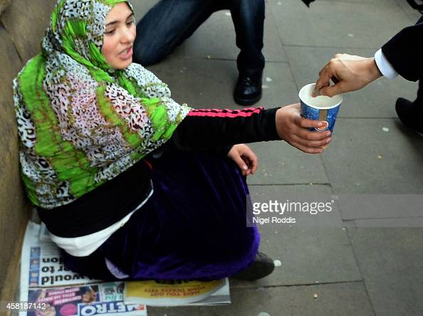Labour leader Ed Miliband donates money to a woman as he walks to a meeting with UK council leaders at the Town Hall on October 31 2014 in Manchester...