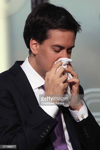 Labour leader Ed Miliband wipes his nose during a break in a television interview at the annual Labour party conference at the Echo Arena on...