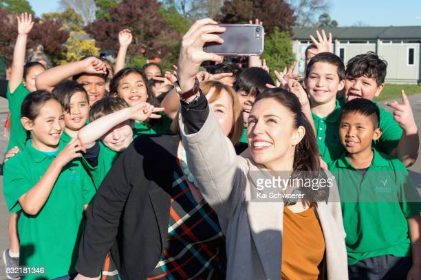 Labour Leader Jacinda Ardern and Labour MP Megan Woods pose with students at Addington Primary School on August 16 2017 in Christchurch New Zealand...