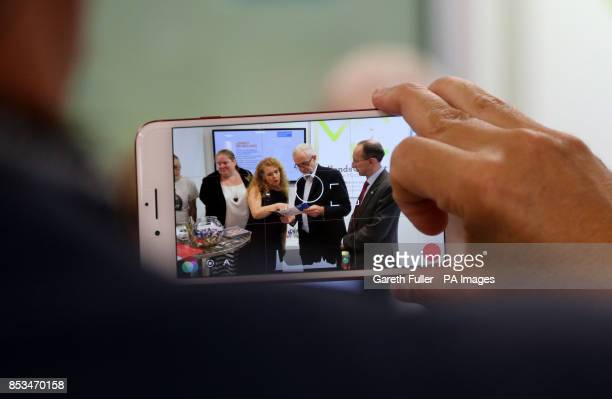 Labour leader Jeremy Corbyn is seen on a mobile phone screen as he visits the exibition stands at the Labour Party conference in Brighton