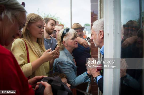 Labour leader Jeremy Corbyn leans out of a window to greet supporters who waited outside the Bournemouth West Cliff Hotel to see him during his visit...