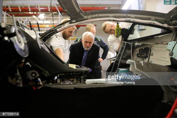 Labour Leader Jeremy Corbyn looks inside a car as he meets workers during a visit to luxury car maker Aston Martin on November 16 2017 in Warwick...
