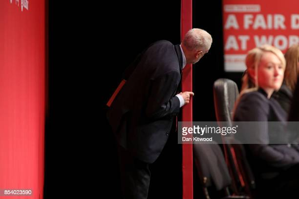 Labour Leader Jeremy Corbyn peers around boarding during speeches in the main hall on day three of the annual Labour Party Conference on September 26...