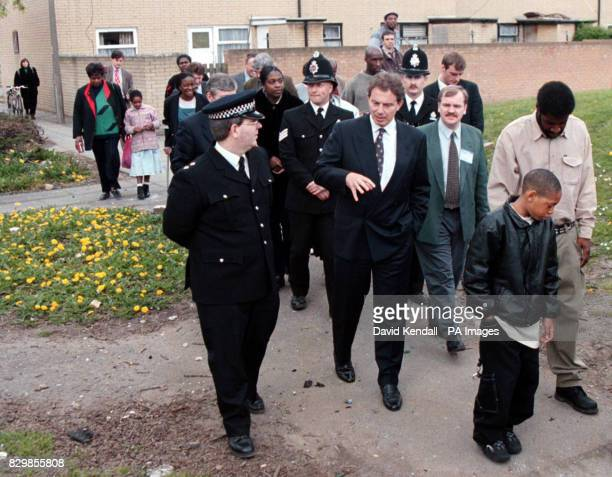 Labour leader Tony Blair accompanied by Insp Nigel Preston left of Greater Manchester Police tours an area of Moss Side Manchester during a vist to...