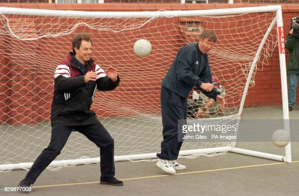 Labour leader Tony Blair parries a shot at goal as Manchester United manager Alex Ferguson attempts a save during a visit today to Devonshire Road...