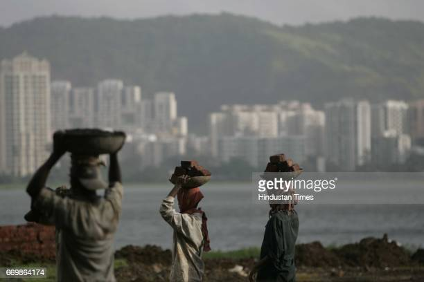 Labour Occupation Worker Housing Real Estate Highrise Buildings Skyscrapers Hiranandani Gardens near Powai Lake in the midst of tall buildings a man...