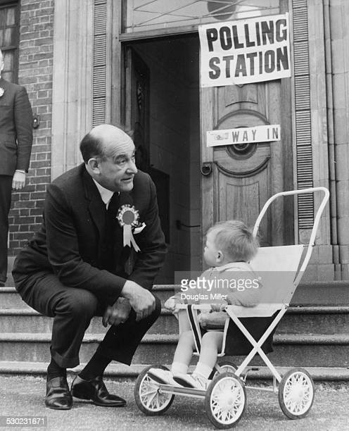 Labour Party candidate Patrick Gordon Walker saying hello to 15 month old John Ruerdi outside a polling station Essex Road Leyton London March 31st...