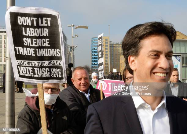 Labour Party Ed Miliband walks past a protest as he arrives at the ExCel Centre in Docklands in east London for a special conference