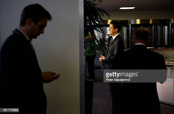 Labour Party leader Ed Miliband gives an early morning television interview as his director of communications Bob Roberts and another aide James...
