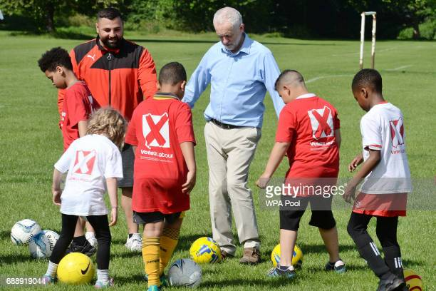 Labour Party leader Jeremy Corbyn plays football with children during a visit to Hackney Marshes Football Pitches to highlight Labour's manifesto...