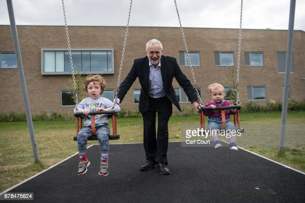 Labour Party leader Jeremy Corbyn pushes Isabella and Freddie the children of local parliamentary candidate Anneliese Dodds during a visit to a play...
