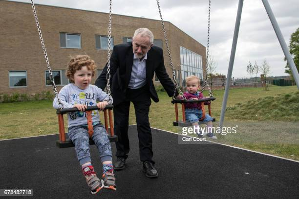 Labour Party leader Jeremy Corbyn pushes Isabella and Freddie the children of local parliamentary candidate Anneliese Dodds on swings during a visit...