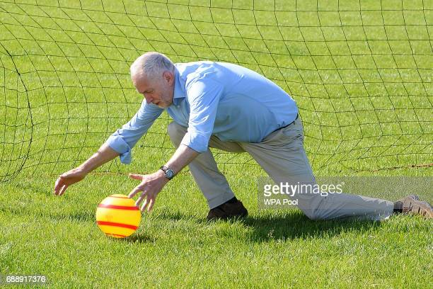 Labour Party leader Jeremy Corbyn saves a penalty kick from a child during a visit to Hackney Marshes Football Pitches to highlight Labour's...