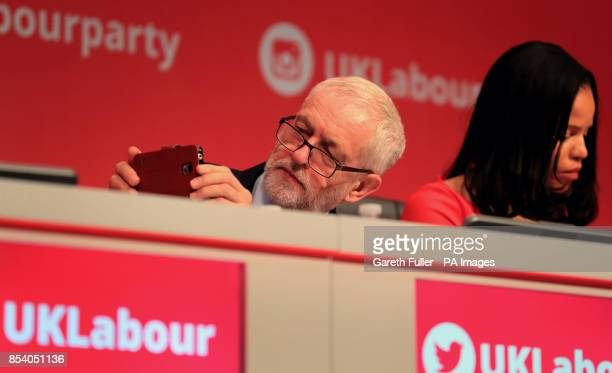 Labour Party leader Jeremy Corbyn takes a photograph as he listens to speeches during their annual conference at the Brighton Centre Brighton