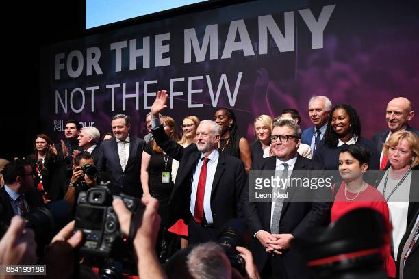 Labour party leader Jeremy Corbyn waves to delegates in the main hall as Deputy Labour party leader Tom Watson and Shadow Attorney General Shami...