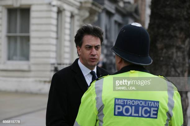 Labour Party politician and former party leader Ed Miliband talks with a police officer on Whitehall in central London near the Houses of Parliament...