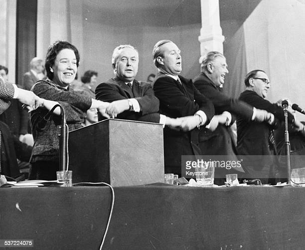 Labour Party politicians joining hands and singing Auld Land Syne Alice Bacon Harold Wilson Mr Greenwood A L Williams and D Davies at the conference...