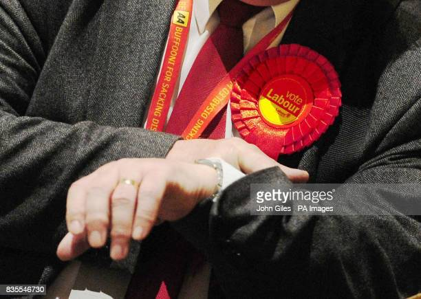 A Labour Party supporter looks at his watch as ballot papers for the Local and European Parliament elections are sorted and counted in Preston