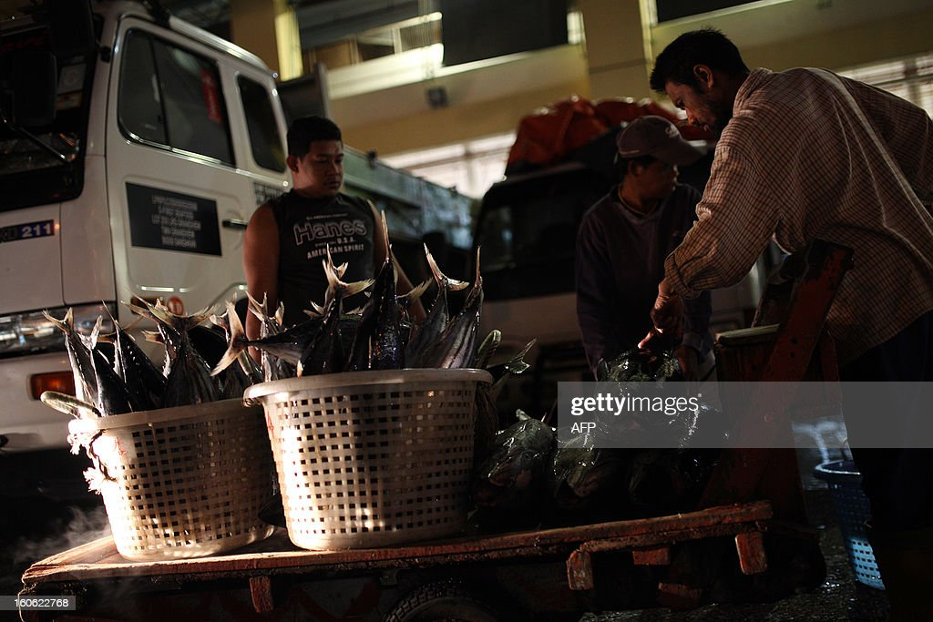 A labour pushes a cart full of the catch of the day towards the trading floor of the Sandakan central fish market in the Malaysian Borneo state of Sabah on February 4, 2013. Sandakan is the second-largest city in Sabah, eastern Malaysia, on the northeastern coast of Borneo. AFP PHOTO / MOHD RASFAN