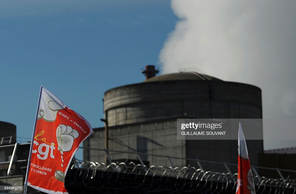 CGT labour union flag is seen on May 26, 2016 at the entrance of the nuclear power plant of Chinon to protest against the government's proposed labour reforms. Workers at nuclear power stations in France were set to go on strike on May 26, joining a growing protest movement against controversial labour market reforms that has already severely disrupted fuel supplies. With two weeks until France hosts the Euro 2016 football championships, the country has been paralysed by a series of transport strikes and fuel shortages that has heaped pressure on the deeply unpopular Socialist government. / AFP / GUILLAUME