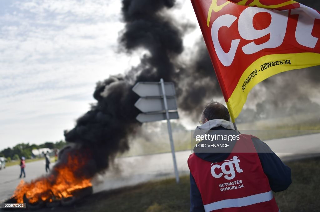 A labour union member holds the CGT (General Confederation of Labour) union flag as he stands next to a pile of tyres set ablaze at a filtering roadblock close to the entrance of the Total refinery of Donges, western France, on May 31, 2016, to protest against the government's planned labour law reforms. / AFP / LOIC