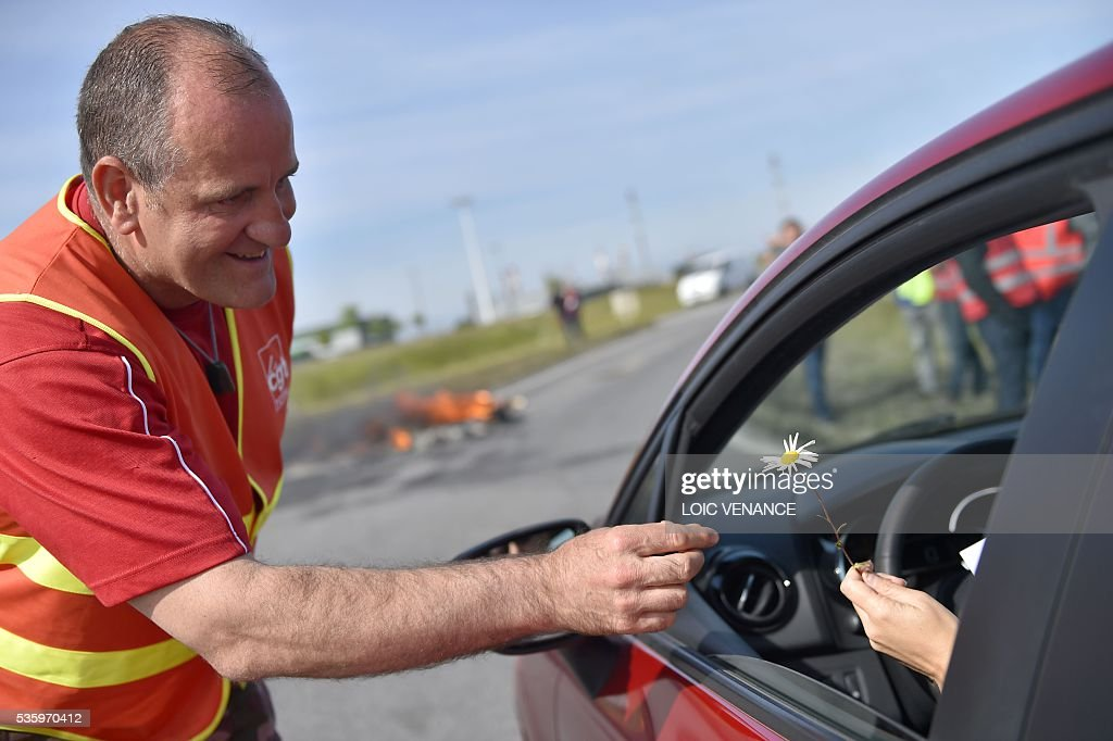 A labour union member offers a flower to a car driver at a filtering roadblock close to the entrance of the Total refinery of Donges, western France, on May 31, 2016, to protest against the government's planned labour law reforms. / AFP / LOIC