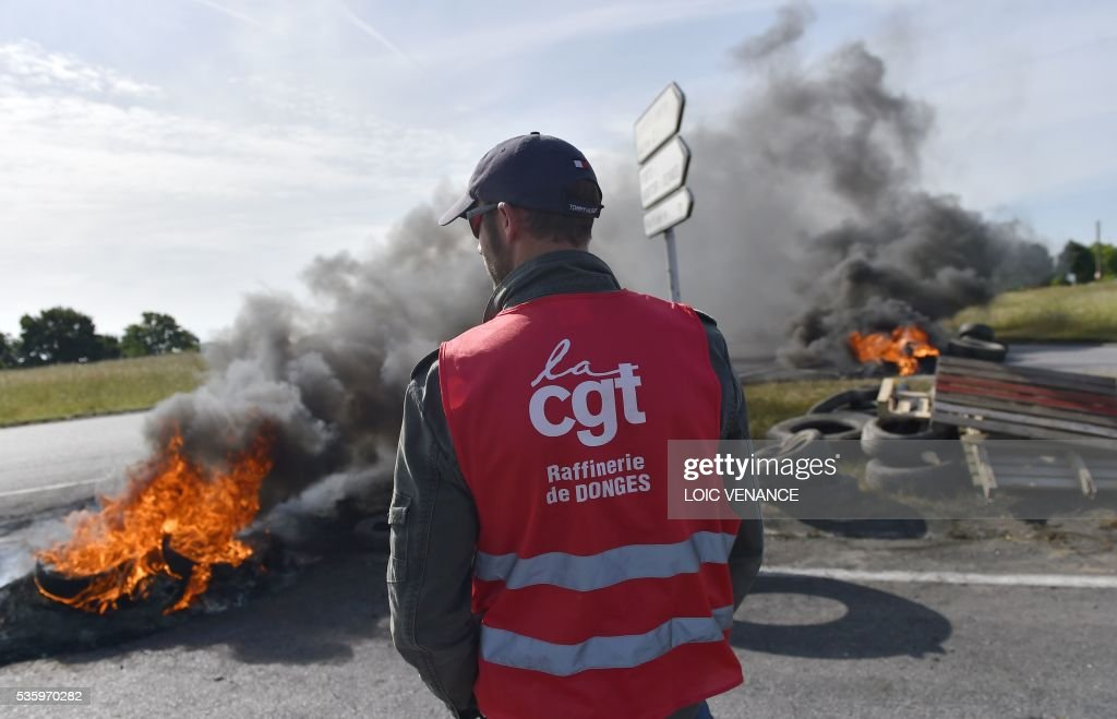A labour union member stands next to a pile of tyres set ablaze at a filtering roadblock close to the entrance of the Total refinery of Donges, western France, on May 31, 2016, to protest against the government's planned labour law reforms. / AFP / LOIC