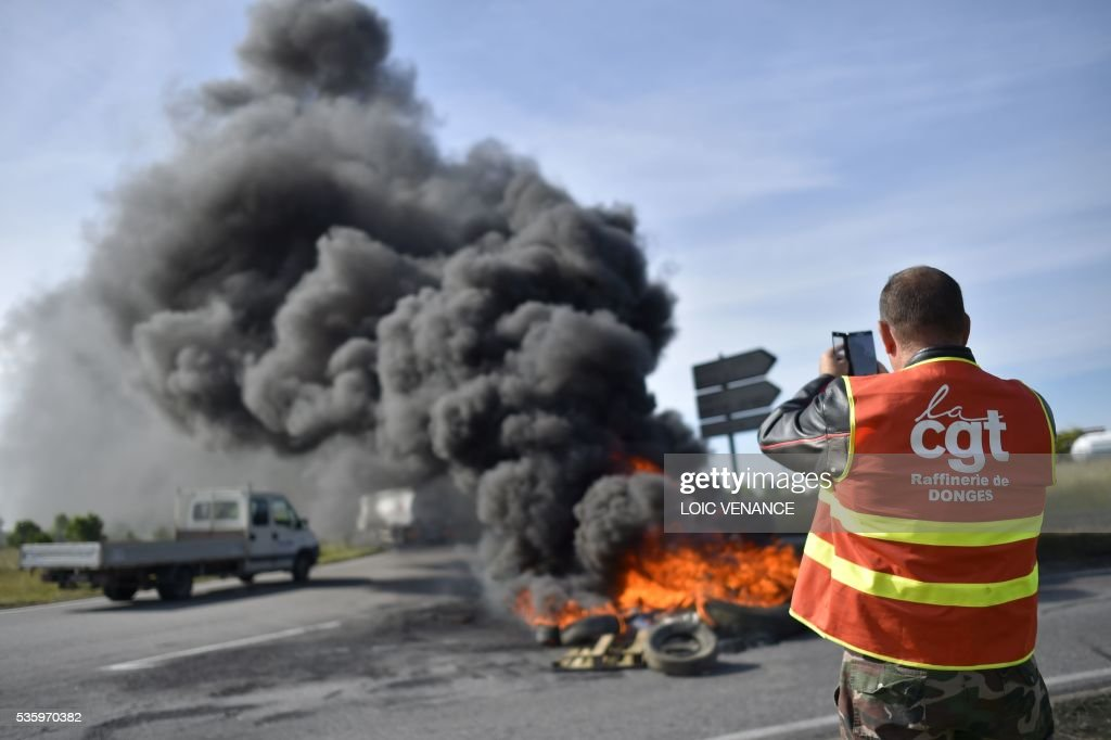 A labour union member takes a photo with his mobile phone of a pile of tyres set ablaze at a filtering roadblock close to the entrance of the Total refinery of Donges, western France, on May 31, 2016, to protest against the government's planned labour law reforms. / AFP / LOIC