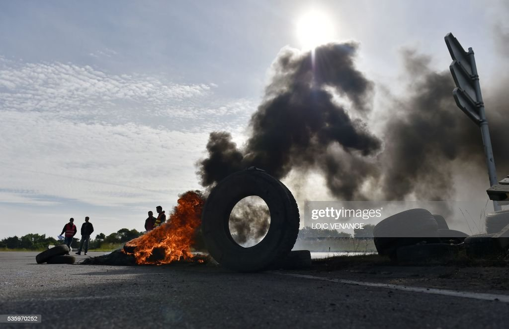 Labour union members stand next to a pile of tyres set ablaze at a filtering roadblock close to the entrance of the Total refinery of Donges, western France, on May 31, 2016, to protest against the government's planned labour law reforms. / AFP / LOIC