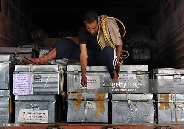 A labourer adjusting boxes containing official records of Jammu and Kashmir states' Civil Secretariat for loading into the trucks on April 30 2016 in...