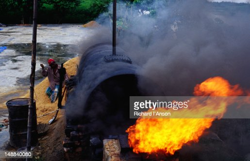 Labourer burning rice husks at rice mill.