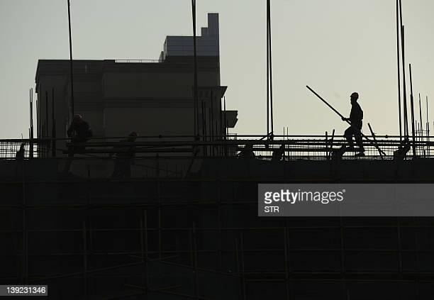 A labourer carries materials at the construction site of a new housing project in Hefei in eastern China's Anhui province on February 18 2012 Home...